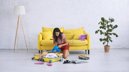 Photo for Brunette woman packing baggage near summer clothes on floor in living room - Royalty Free Image
