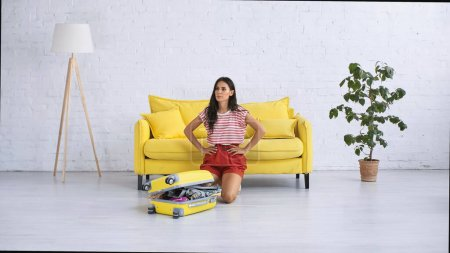 Photo for Tired woman sitting near baggage with clothes on floor in living room - Royalty Free Image