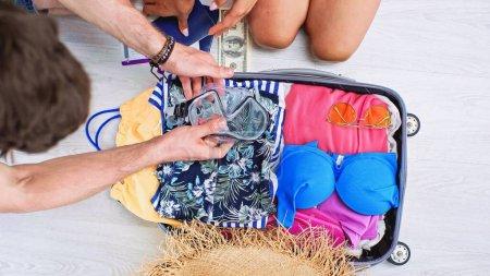 Photo pour Vue recadrée du couple près des bagages avec vêtements d'été, argent, passeports et billets de voyage - image libre de droit
