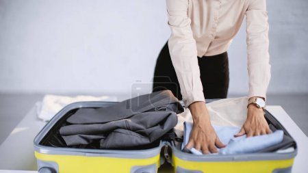 Photo for Cropped view of businesswoman packing clothes in baggage at home - Royalty Free Image