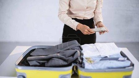 Photo pour Vue recadrée de femme d'affaires tenant de l'argent tout en emballant la valise à la maison - image libre de droit