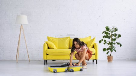 Photo for Brunette woman packing yellow suitcase near couch in living room - Royalty Free Image