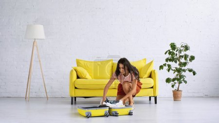 Photo for Brunette woman packing yellow suitcase near sofa in living room - Royalty Free Image