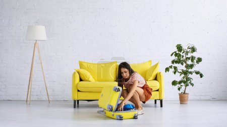 Photo for Brunette woman packing yellow travel bag near couch in living room - Royalty Free Image