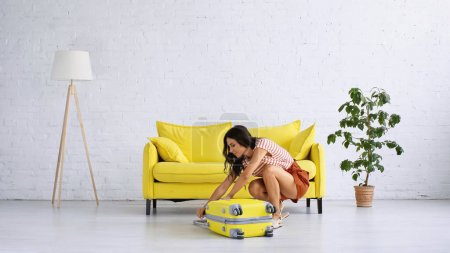 brunette woman closing yellow travel bag near couch in living room