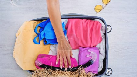 partial view of woman packing suitcase with summer clothes at home