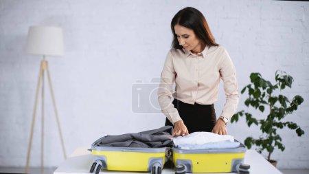 Photo pour Brunette femme d'affaires emballage jaune valise à la maison - image libre de droit