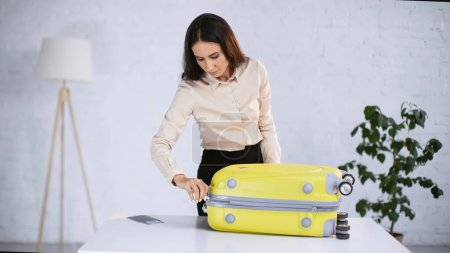 Photo for Brunette businesswoman zipping yellow suitcase - Royalty Free Image