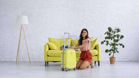 Photo for Happy woman sitting near yellow baggage at home - Royalty Free Image