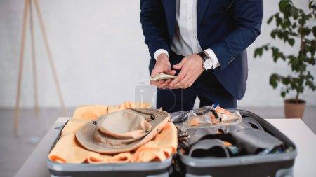 Photo pour Vue recadrée de l'homme d'affaires en costume tenant de l'argent lors de l'emballage des bagages - image libre de droit