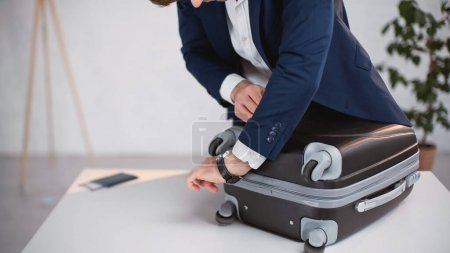 Photo for Cropped view of businessman in suit zipping luggage - Royalty Free Image