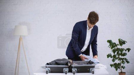 Photo pour Homme d'affaires en costume d'emballage de vêtements dans la valise à la maison - image libre de droit