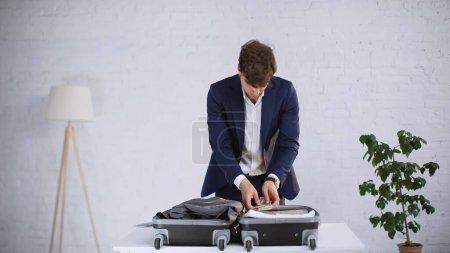 Photo pour Homme d'affaires en costume tenant des dollars tout en emballant des vêtements dans la valise à la maison - image libre de droit