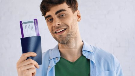 Photo for Happy man in blue shirt holding passport with air ticket - Royalty Free Image