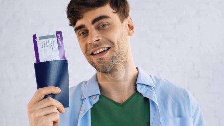 glücklicher Mann im blauen Hemd mit Pass und Flugticket