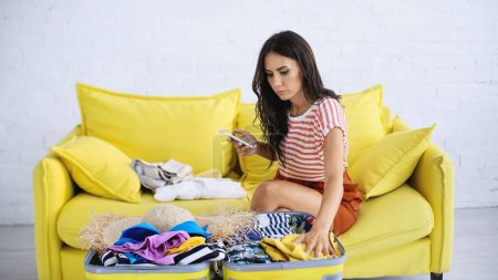 Photo for Brunette woman holding smartphone while packing suitcase - Royalty Free Image