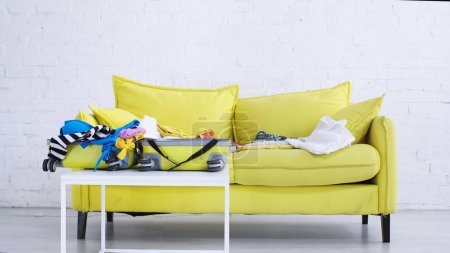 Photo for Travel bag with casual clothing on coffee table near yellow couch - Royalty Free Image