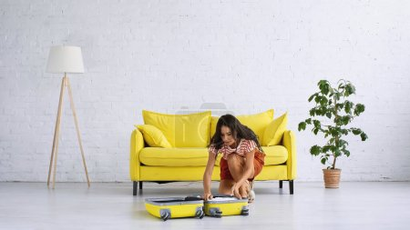 brunette woman sitting near yellow suitcase and sofa in living room
