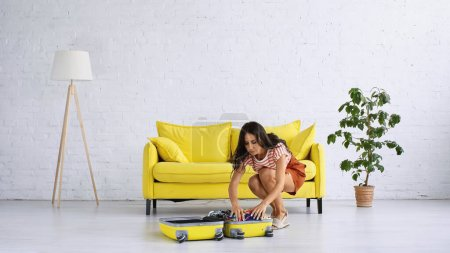 Photo for Brunette woman packing clothing while sitting near yellow suitcase and sofa in living room - Royalty Free Image