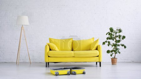 yellow sofa near floor lamp, plant and suitcase on floor