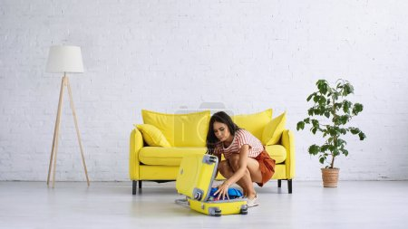 Photo for Brunette woman sitting and packing yellow suitcase near sofa in living room - Royalty Free Image