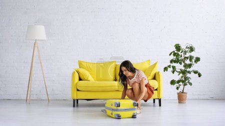 Photo for Brunette woman sitting and zipping yellow suitcase near sofa in living room - Royalty Free Image