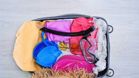 Photo for Top view of packed suitcase with summer clothes and sunglasses - Royalty Free Image