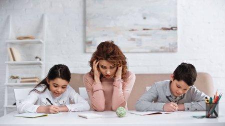 Photo pour Femme assise près des enfants écrivant sur des cahiers pendant leurs devoirs - image libre de droit