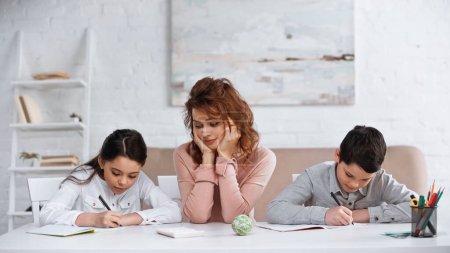 Photo pour Mère aidant les enfants à écrire sur des cahiers pendant leurs devoirs - image libre de droit