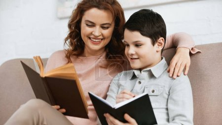 Photo for Cheerful woman reading book while helping son with homework - Royalty Free Image