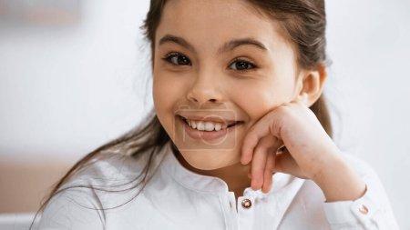 Positive preteen kid smiling at camera