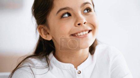 Photo pour Souriante fille regardant vers le haut à la maison - image libre de droit