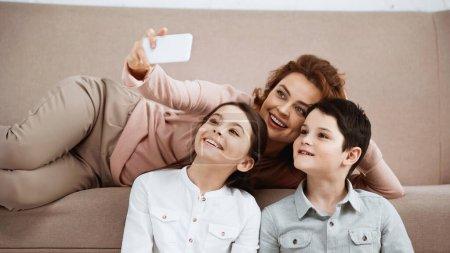 Photo pour Mère souriante prenant selfie avec des enfants à la maison - image libre de droit