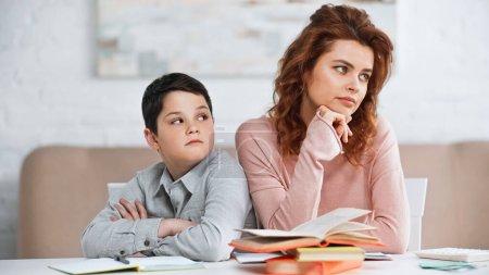 Photo pour Fils avec les bras croisés regardant mère triste près des livres sur la table - image libre de droit