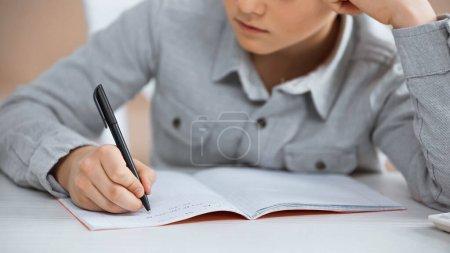 Photo pour Vue recadrée de garçon écrivant sur copie livre à la maison - image libre de droit