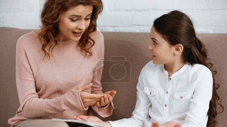 Photo pour Femme parlant près de fille avec ordinateur portable sur le canapé - image libre de droit
