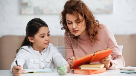 Photo for Woman holding book near daughter with pen on blurred foreground - Royalty Free Image