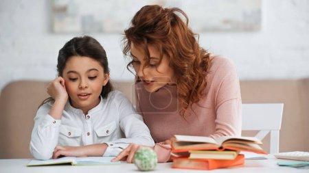 Photo pour Femme parlant à sa fille tout en aidant aux devoirs près des livres - image libre de droit
