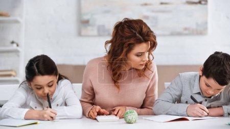 Mutter hilft Kindern bei Hausaufgaben nahe Taschenrechner auf dem Tisch