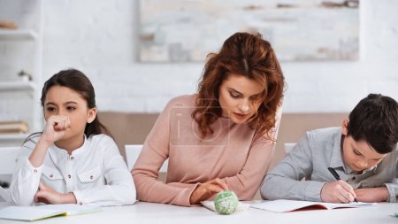 Woman using calculator near pensive daughter and son writing on notebook at home