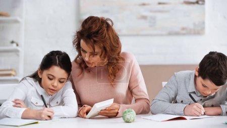 Photo pour Femme tenant la calculatrice près des enfants écrivant sur des cahiers à la maison - image libre de droit