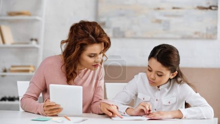 Photo for Woman with digital tablet pointing at notebook near daughter doing homework - Royalty Free Image