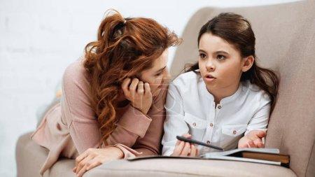 Photo pour Fille parler près de mère et ordinateur portable tout en faisant des devoirs sur le canapé - image libre de droit