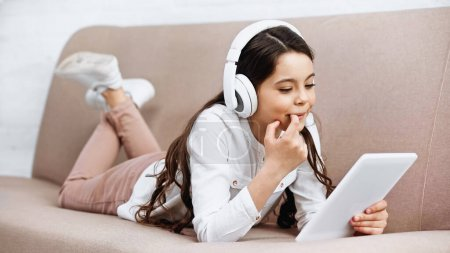 Photo for Smiling kid using headphones and digital tablet on couch in living room - Royalty Free Image