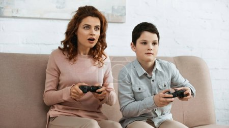 Photo for KYIV, UKRAINE -  APRIL 15, 2019: Excited mother playing video game with son on couch - Royalty Free Image