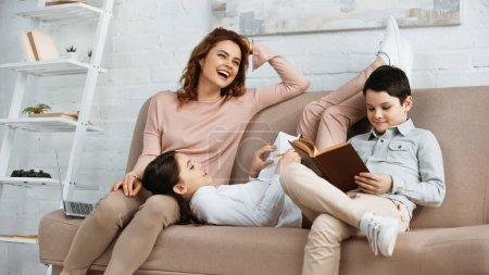 Photo pour Mère joyeuse assise sur le canapé près des enfants avec un livre et un cahier à la maison - image libre de droit
