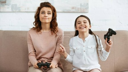 Photo for KYIV, UKRAINE -  APRIL 15, 2019: Smiling daughter holding joystick near sad mother on couch - Royalty Free Image