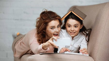 Photo for Mother and daughter taking selfie on smartphone with book and notebook on couch - Royalty Free Image