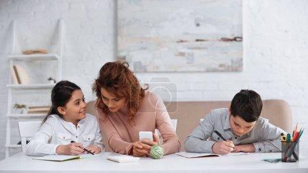 Photo pour Enfant souriant parlant à sa mère avec son smartphone tout en faisant ses devoirs avec son frère - image libre de droit