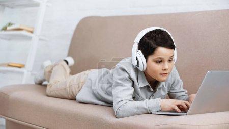 Photo pour Preteen garçon dans les écouteurs en utilisant un ordinateur portable sur le canapé - image libre de droit